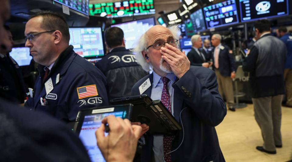 Traders and financial professionals work ahead of the closing bell on the floor of the New York Stock Exchange on March 26.