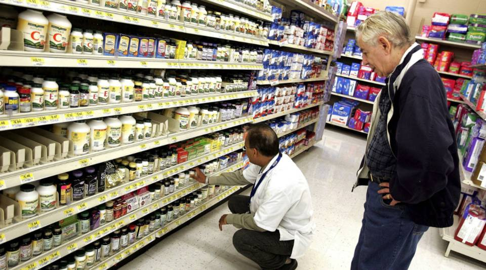 A pharmacy manager assists a shopper in the pharmacy area of a Walmart store in Mount Prospect, Illinois.