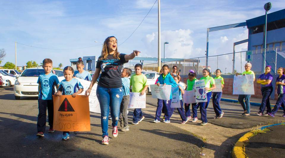 Second grade teacher Pierette Hidalgo leads students and parents in a chant during a school closing protest at Escuela Elemental John F. Kennedy in Toa Baja, Puerto Rico on April 17, 2018. The school is one of 283 schools slated to be close on the island following population declines.