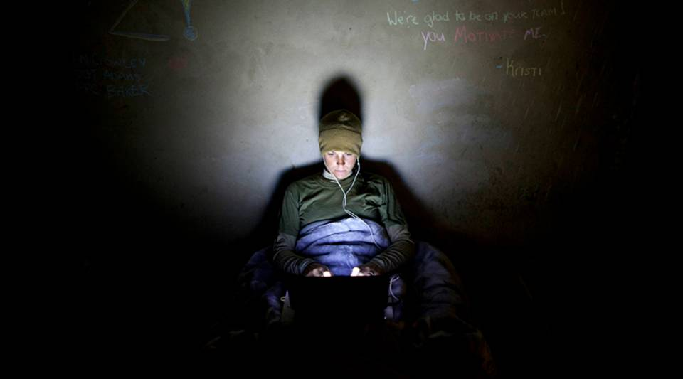 A US Marine with the FET (Female Engagement Team) 1st Battalion 8th Marines, Regimental Combat team II works late into the night on her laptop on her reports on November 12, 2010 in Musa Qala, Afghanistan.