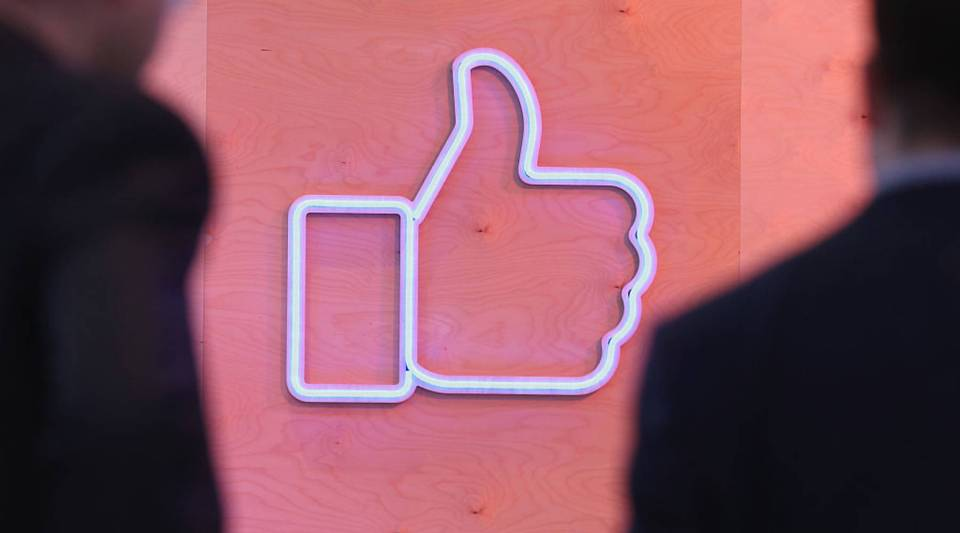 People walk past the Facebook 'Like' symbol at the Facebook Innovation Hub on Feb. 24, 2016 in Berlin, Germany.