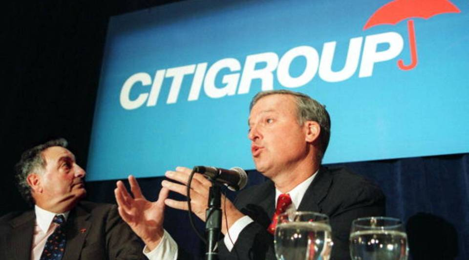 Sanford Weill, chairman and CEO of Travelers Group, turns to look at the new Citigroup company logo as John Reed, chairman and CEO of Citicorp, addresses a press conference on April 6, 1998, in New York.