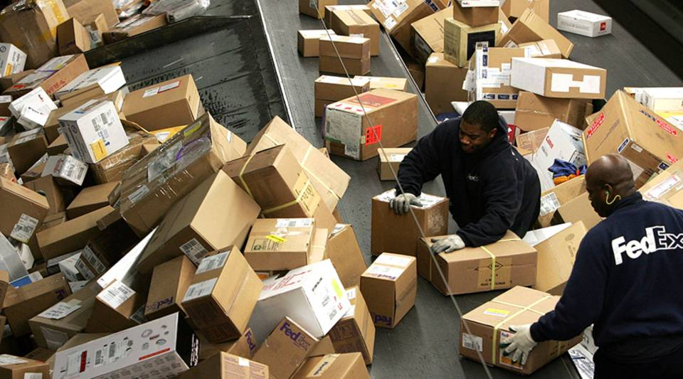 FedEx worker sort through a pile of boxes at the FedEx sort facility at the Oakland International Airport in December 2006 in California.