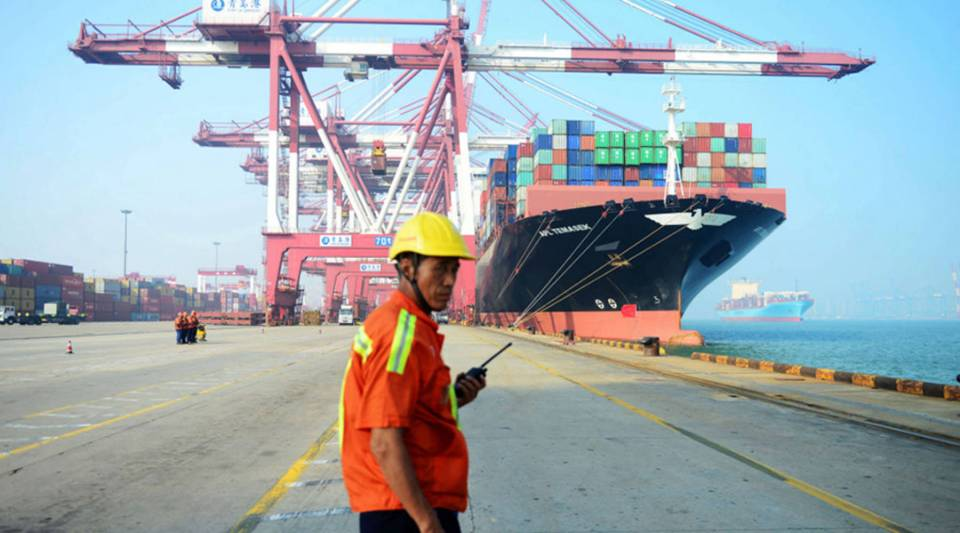 A Chinese worker looks on as a cargo ship is loaded at a port in Qingdao in eastern China's Shandong province in July.