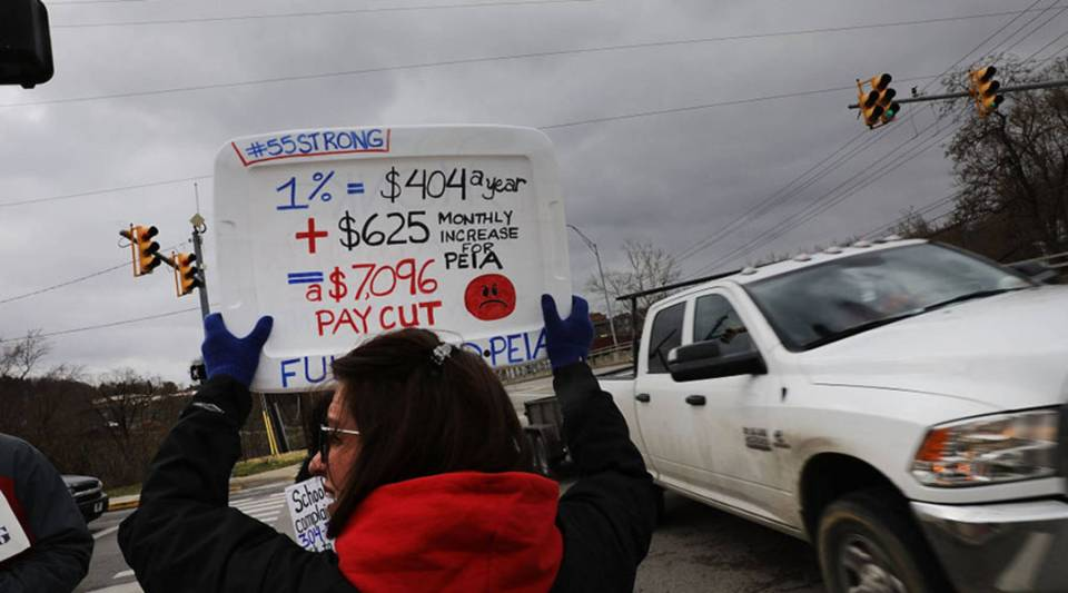 West Virginia teachers, students and supporters hold signs on a Morgantown street as they continue their strike on March 2.