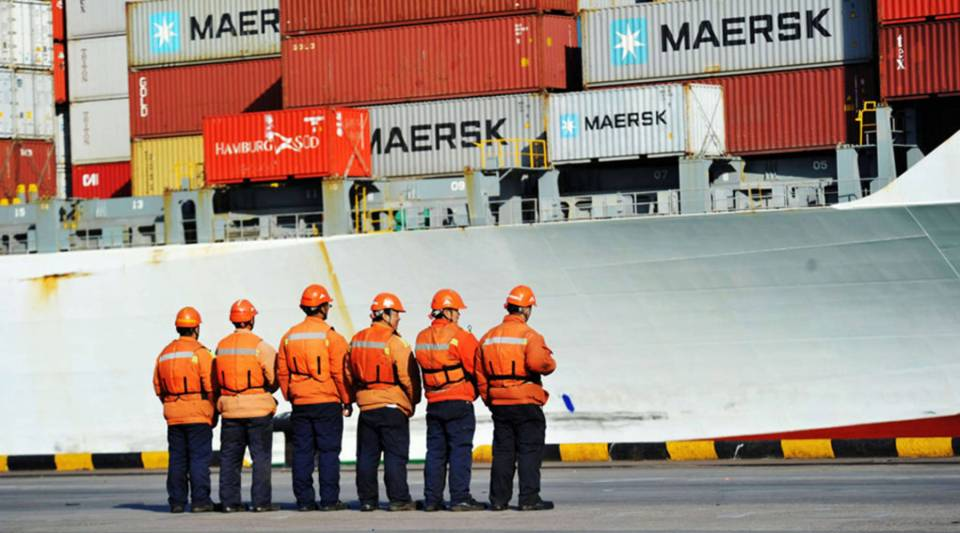 Workers stand in line next to a container ship at a port in Qingdao in China's eastern Shandong province earlier this month.