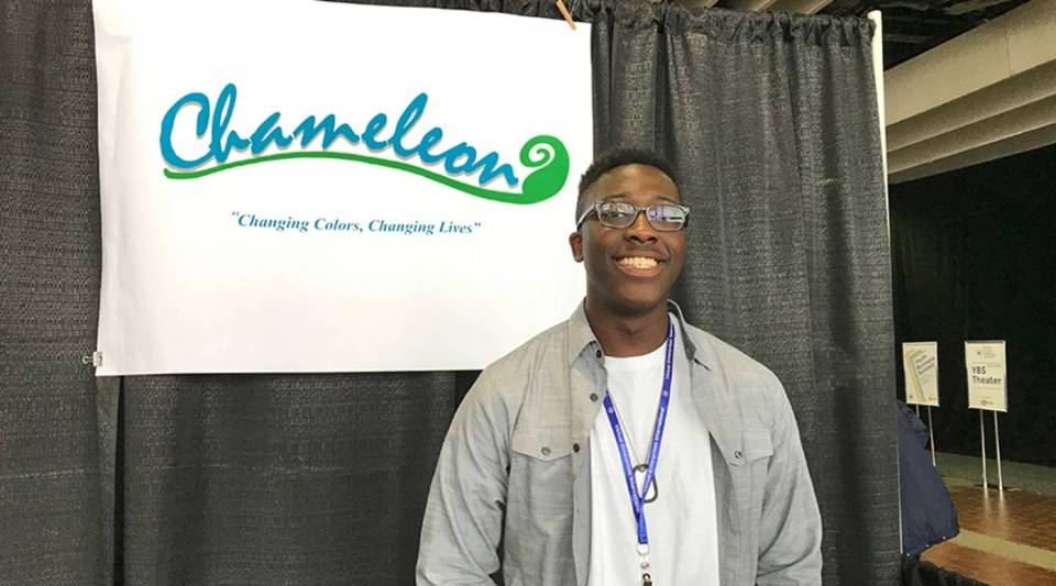 Emauri Singletary in front of the logo he designed for his Virtual Enterprise company, which sells disposable cups that change color to detect date rape drugs.