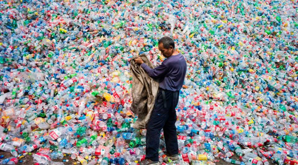 A Chinese laborer sorts plastic bottles for recycling in Dong Xiao Kou village on the outskirts of Beijing.