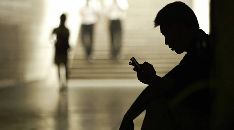 A man uses his mobile phone for messaging in an underpass in Beijing 20 July 2004.