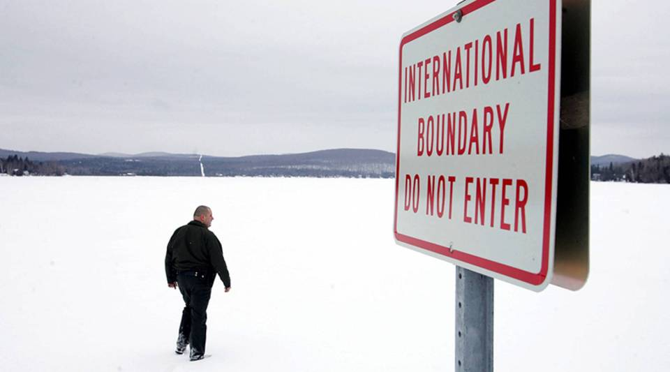 A U.S. Border Patrol agent walks onto a frozen lake that is split between Canadian territory to the right and the United States in 2006 near Norton, Vermont.