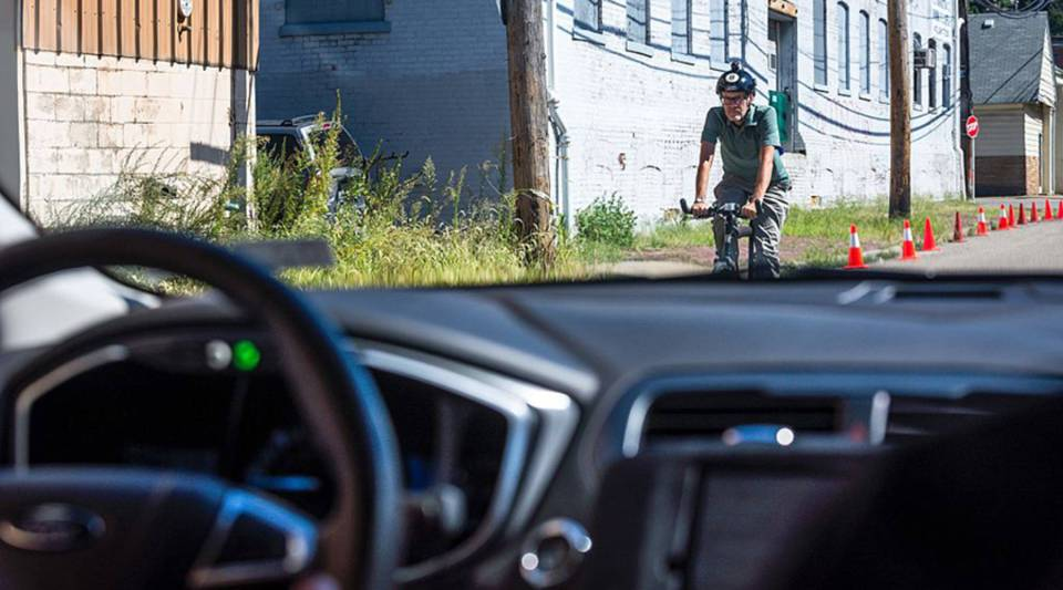 A biker passes a pilot model of the Uber self-driving car in 2016 in Pittsburgh, Pennsylvania.