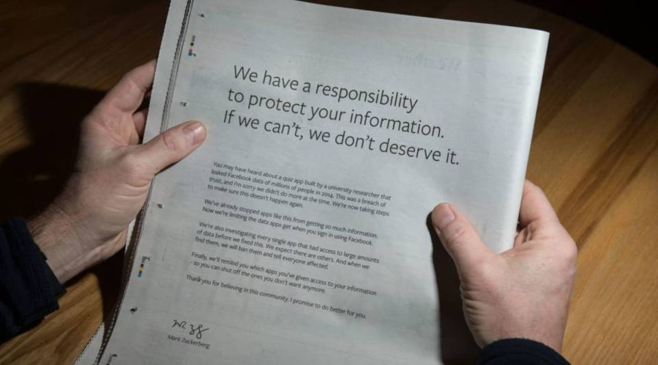 A man reads a full-page advertisement, taken out by Mark Zuckerberg, the chairman and chief executive officer of Facebook to apologize for the large-scale leak of personal data from the social network on March 25, 2018.