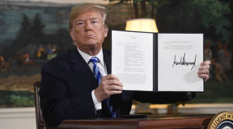 President Donald Trump signs a document reinstating sanctions against Iran after announcing the U.S. withdrawal from the Iran Nuclear deal, in the Diplomatic Reception Room at the White House in Washington, D.C., on May 8, 2018.