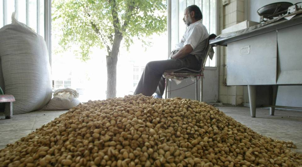 Iranian Mohammad Reza Saberi sits by a mound of pistachios in his shop in Rafsanjan, Iran.