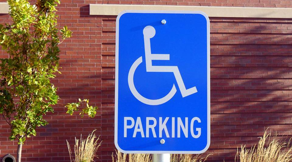 [Image Description: A close up shot of a bright blue handicapped parking sign. In the background is a tree and other vegetation in front of a red brick wall.]
