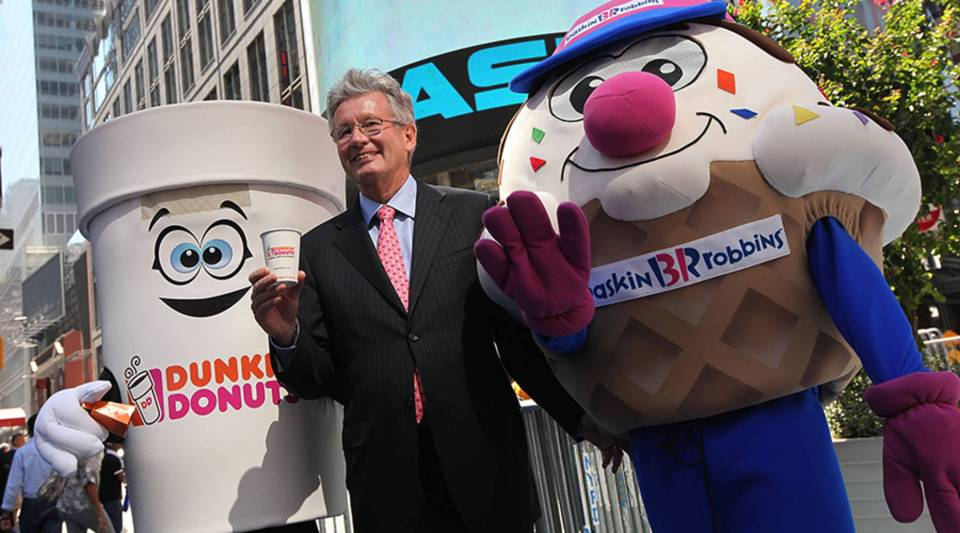 Nigel Travis, president and CEO of Dunkin' Brands, the parent company of Dunkin' Donuts and Baskin-Robbins, celebrates the initial public offering with some friends outside the NASDAQ MarketSite on July 27, 2011, in New York City.