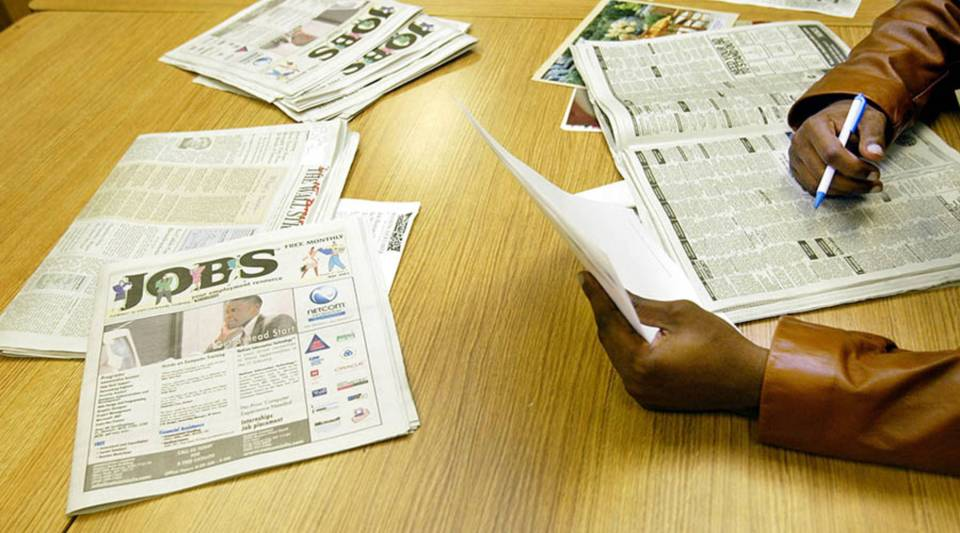 [Image Description: An individual is sitting at a desk, searching through a newspaper's help wanted ads. They are wearing a brown jacket, and are holding a pen in one hand and a sheet of white paper in the other.]
