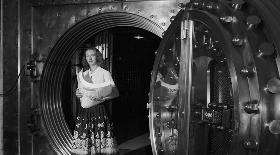An office worker, circa 1955, fetches bond certificates from the vault of the Toronto General Trusts Corp., which is secured by a massive fifteen ton door.