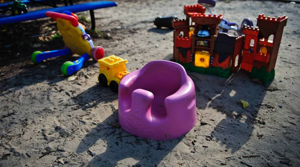 [Image Description: Numerous toys are spread across a child's playground. The ground is sandy. A pink children's seat is in the middle of the image, with a yellow toy truck and multi-colored doll house behind it. In the background is a blue set of benches.]
