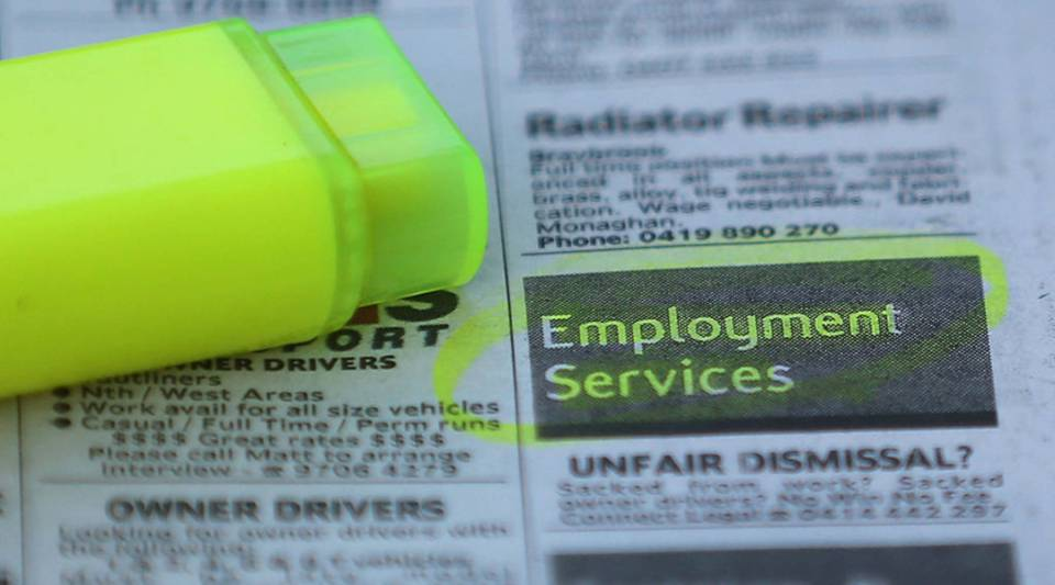 """[Image Description: A close-up shot of a black and white printed jobs section in a newspaper. A yellow highlighter sits on top of the newspaper. The words """"Employment Services"""" are placed in a black box and have been highlighted and circled.]"""