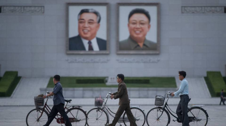 Men push their bicycles past portraits of late North Korean leaders Kim Il Sung, left, and Kim Jong Il in Pyongyang in 2017.
