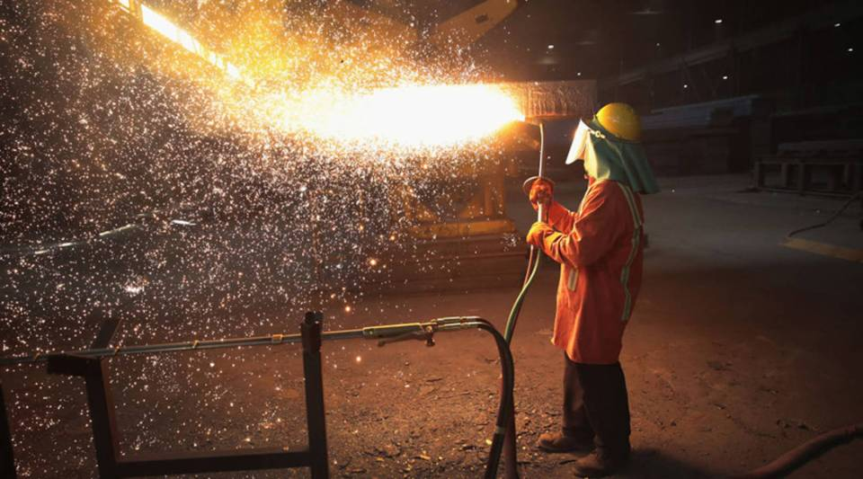A worker trims a newly cast steel slab at the NLMK Indiana steel mill in March in Portage, Indiana.