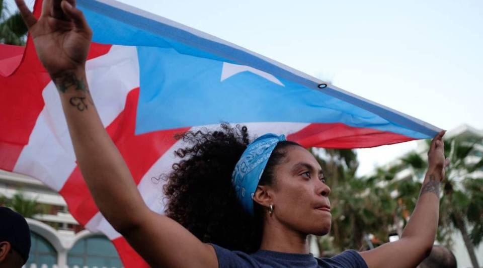 People march to protest pension cuts, school closures and slow hurricane recovery efforts in San Juan, Puerto Rico in May.