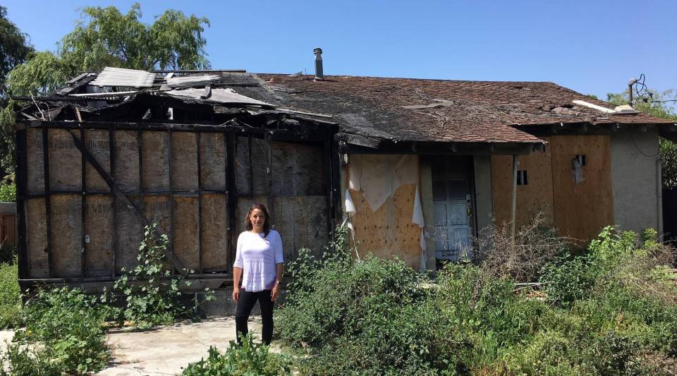 San Jose real estate agent Holly Barr stands outside the burned-out house she sold for more than $900,000.