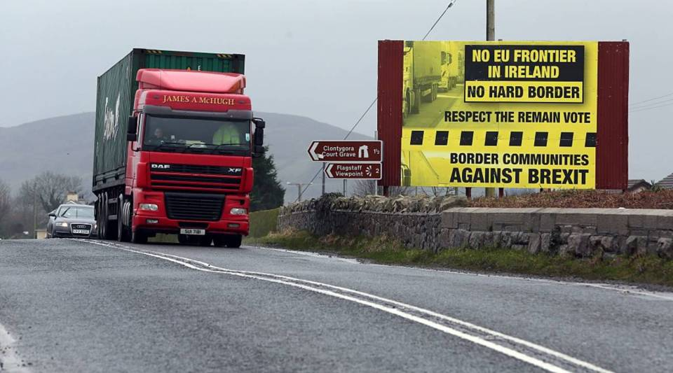 Traffic crosses the border into Northern Ireland from the Irish Republic next to a poster protesting a hard Brexit.