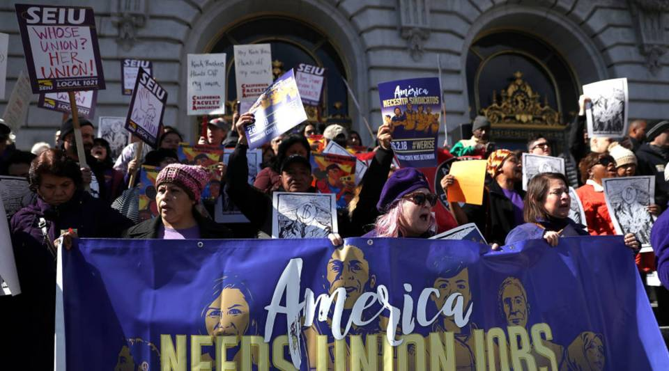 Union members held signs during a rally outside of San Francisco City Hall on Feb. 26 in San Francisco, California, as the U.S. Supreme Court began to hear oral arguments in the Janus V. AFSCME case.