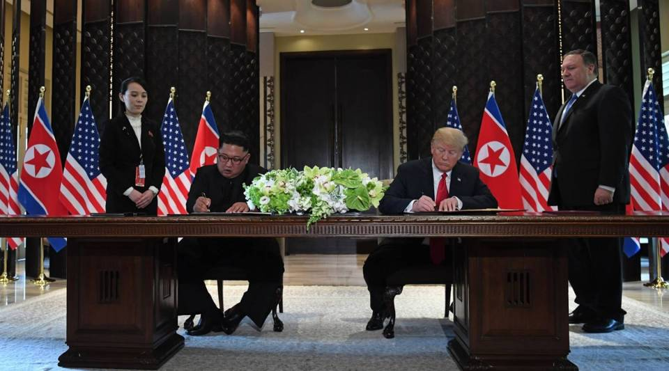 North Korea's leader Kim Jong Un and U.S. President Donald Trump sign documents as U.S. Secretary of State Mike Pompeo (R) and Kim Jong Un's sister, Kim Yo Jong, look on at a signing ceremony during their historic U.S.-North Korea summit.