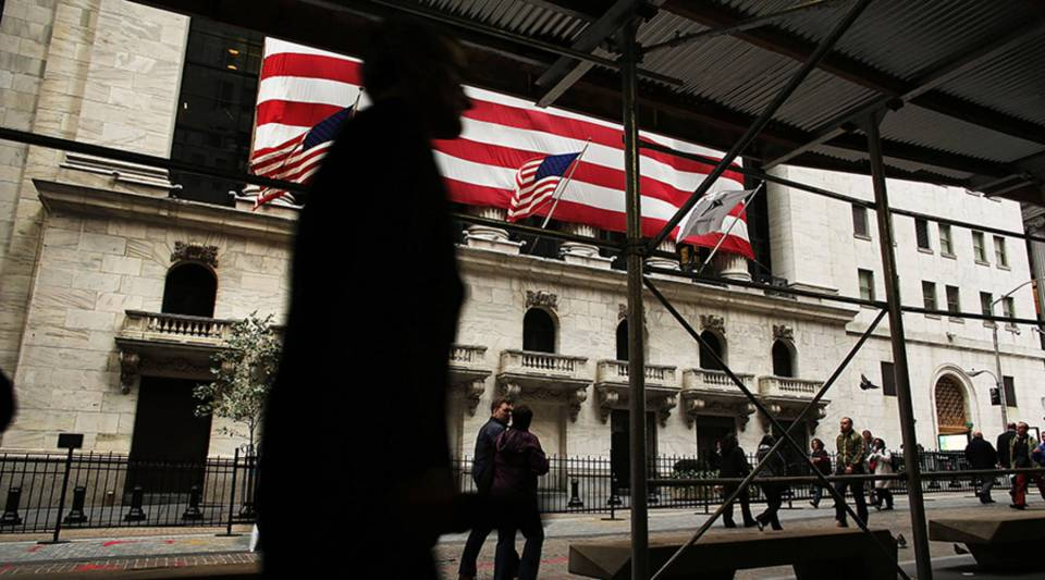 People walk by the New York Stock Exchange in the financial district of Manhattan in 2012.