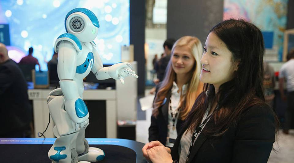 A hostess talks to a NAO Watson robot at the IBM stand at the 2016 CeBIT digital technology trade fair in Hanover, Germany.
