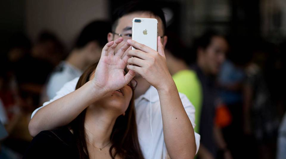 A Chinese couple tests the new iPhone 7 during the opening sale launch at an Apple store in Shanghai on September 16, 2016.