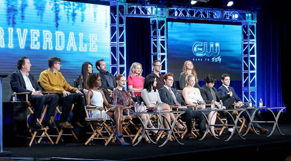 """(L-R front row) The cast Ashleigh Murray, Madelaine Petsch, Camila Mendes, KJ Apa, Lili Reinhart, Cole Sprouse and Casey Cott, back row left to right) Jon Goldwater, Roberto Aguirre-Sacasa, Marisol Nichols, Luke Perry, Madchen Amick, Greg Berlanti and Sarah Schechter of the """"Riverdale"""" television show speak during the CW portion of the 2017 Winter Television Critics Association Press Tour at the Langham Hotel on Jan. 8, 2017 in Pasadena, California."""