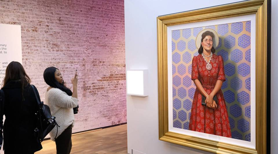 """Attendees admire a painting of Henrietta Lacks at HBO's The HeLa Project Exhibit For """"The Immortal Life of Henrietta Lacks"""" on April 6, 2017 in New York City."""