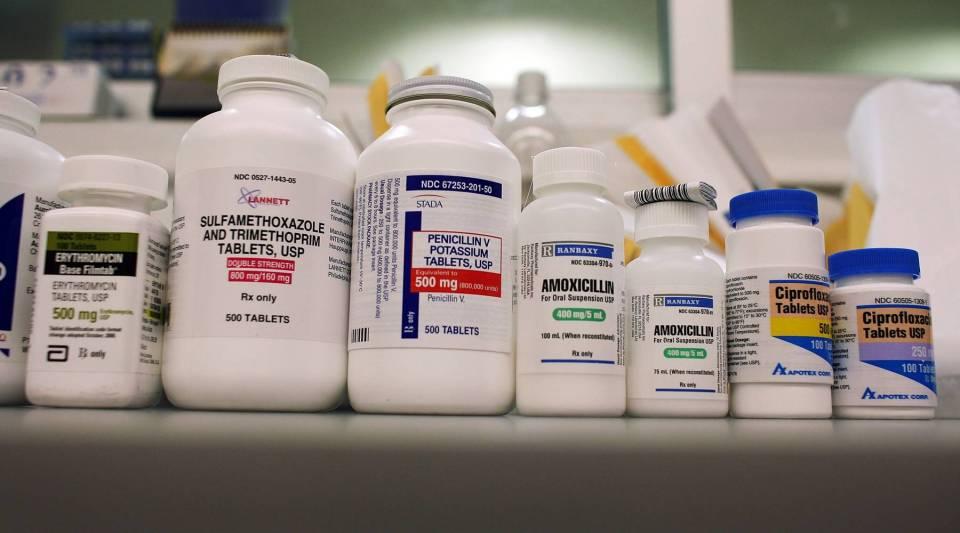 Bottles of antibiotics line a shelf.