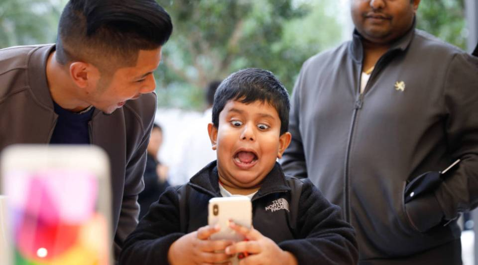 A boy makes faces while testing out the Animoji feature on an iPhone X at the Apple Store Union Square on in San Francisco in 2017.