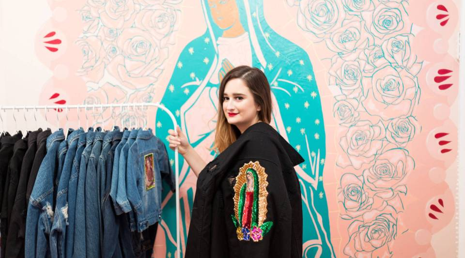 Patty Delgado, founder of Hija de tu Madre, poses next to her signature denim jackets in her Los Angeles showroom.