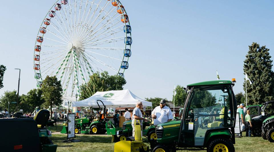 A FerrisWheel turns as people check out John Deere tractors on Machinery Hill at the Minnesota State Fair in Falcon Heights, Minn. on Thursday, Aug. 23, 2018.
