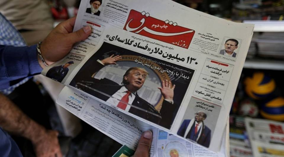 A man takes a glance at a newspaper with a picture of US president Donald Trump on the front page, in the capital Tehran on July 31, 2018. - Iran's currency traded at a fresh record-low of 119,000 to the dollar today, a loss of nearly two-thirds of its value since the start of the year as US sanctions loom.