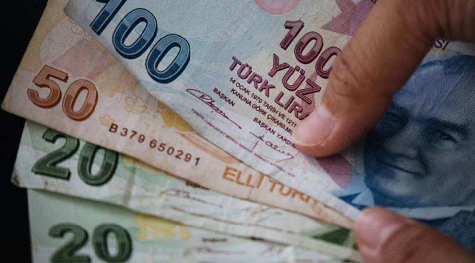 A woman poses for a photograph with Turkish Lira currency on Aug. 13, 2018 in Istanbul, Turkey.The lira hit another record low overnight forcing Turkey's Central Bank to act to curb the lira's collapse however the action was not enough to subdue investors fears over the countries financial crisis.