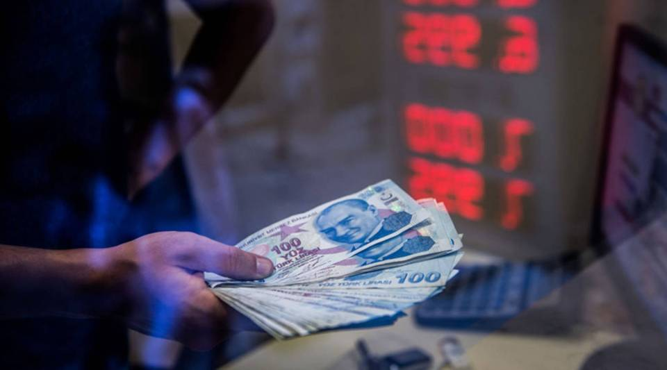 A teller holds Turkish lira banknotes at a currency exchange office in Istanbul on August 13, 2018.