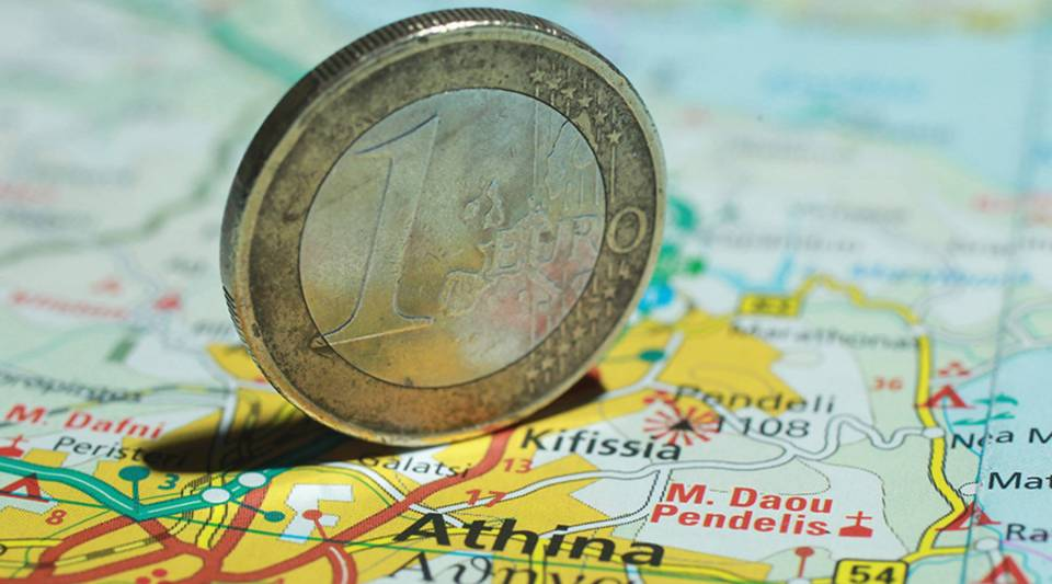 In this photo illustration, a one euro coin stands on a map of Greece showing the city of Athens.
