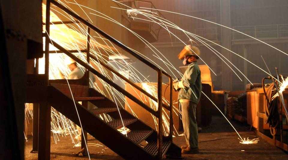 A worker is surrounded by sparks from molten steel flowing into casts at the TAMCO steel mini mill in Rancho Cucamonga, California, in 2002.