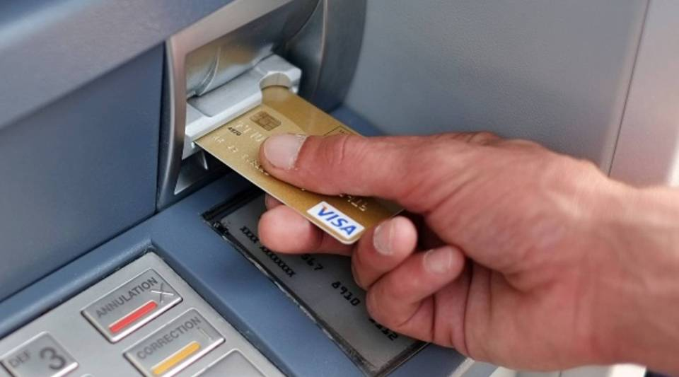 A man takes out Euro banknotes from an automated teller machine.