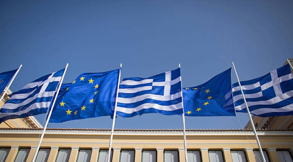 The Greek flag and the flag of the European Union fly above a government building in Athens, Greece.
