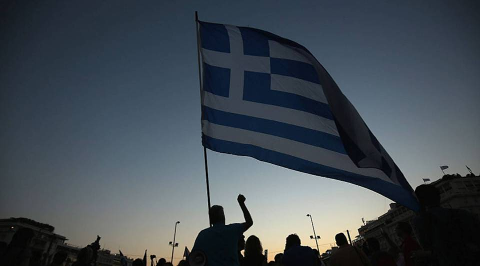 A man waves a Greek flag in front of the Greek parliament during a pro-European rally on July 9, 2015 in Athens, Greece.