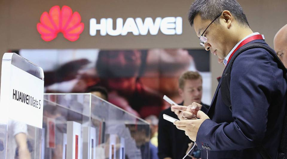 Visitors try out Huawei smartphones at the 2015 IFA consumer electronics and appliances trade fair in Berlin.