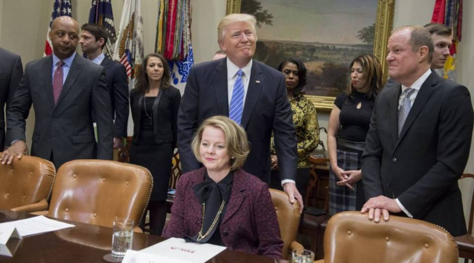 President Donald Trump pushes in the chair for Jill Soltau, CEO of Jo-Ann Stores, as he arrives to meet with retail industry leaders in the Roosevelt Room of the White House in 2017.